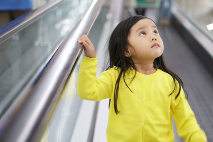 Asian children cute or kid girl down the long escalator alone in department store or supermarket for shopping and looking at the top with wearing yellow shirt