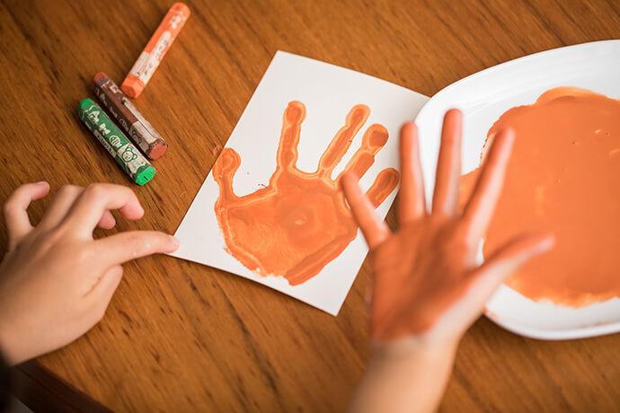 手のひらに、水で薄めた絵の具を付け、ハガキにペタン。手形をドライヤーで乾かします。