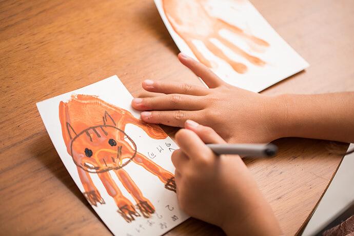 手形をイノシシに見立ててイノシシの顔やひづめを描き、新年のあいさつ文を添えました。