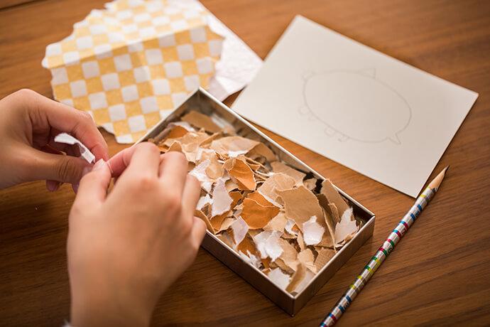 鉛筆でハガキいっぱいにイノシシの顔や体を下書き。折り紙や包装紙は、いろいろな形にちぎっておきます。