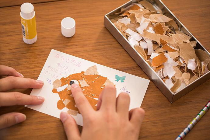 イノシシの毛並に見えるように、ちぎった折り紙や包装紙をのりで貼り、白い紙に黒丸を書いた目もペタリ。