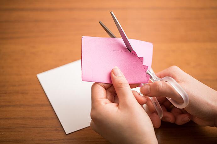 ハガキサイズのピンクの厚紙を半分に折って半円を鉛筆で描き、その線に沿ってギザギザにカット。ステンシルシートの完成です。