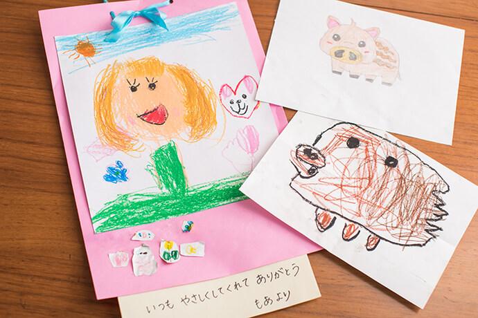 萌愛ちゃんが母の日に描いてくれた絵や姉妹が描いた「干支のイノシシ」の絵。写真は今年のベストショットをチョイス。